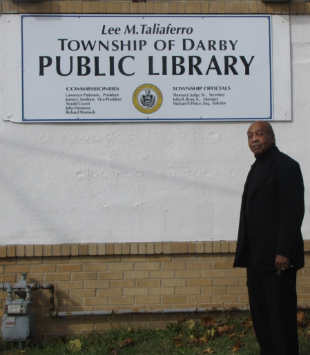 Longtime Darby Township official, Lee Taliaferro standing outside of the town's library recently named in his honor.